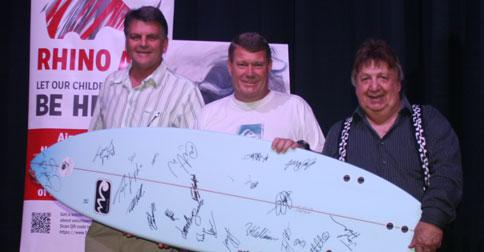 Grant Fols of Rhino Art receives the surfboard donated to the cause by Ballito local Geoff Southwood with comedy musician Eddie Ecksteen.