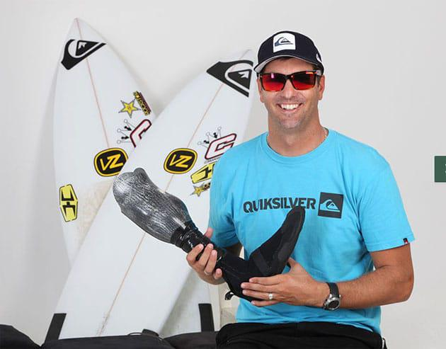JP Veaudry holding the custom surfing prosthetic made for him by Roland Toogood