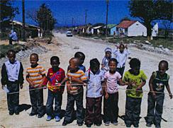 In Clarkson's safe but dusty streets, the children play with a skipping rope