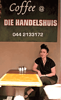 Tracy Farrell at Die Handelshuis, with the sign painted by Marinda Combrink.