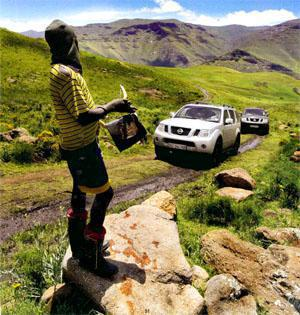 With his highly fashionable gum boots, and the Lesotho version of a Fender Stratocaster guitar in hand, a local man aims to entertain as the Pathfinder V9X convoy makes its way through the slippery Khubelu Valley.