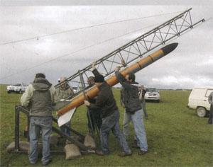 Onlookers help to rig the rocket for launch.