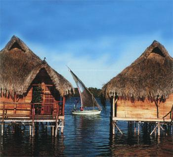 A traditional dhow glides between two of the stilted chalets at Flamingo Bay Water Lodge, Inhambane, Mozambique.