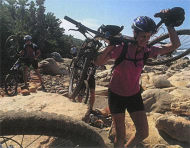 Karin Meyer carries her bike over a rocky section of the Pondoland coastline
