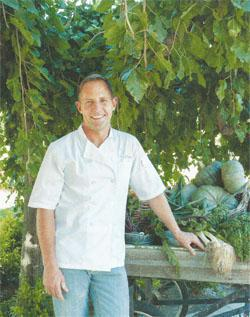Chef Jaco Brand with a cartload of fresh vegetables from the permaculture garden.