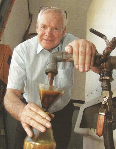 Inventor William Graham decants some of his multi-fuel into a plastic bottle he'll use later as feedstock.