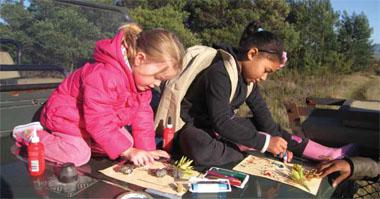 Ruby (left) and a fellow junior ranger get creative with glitter glue and flowers.