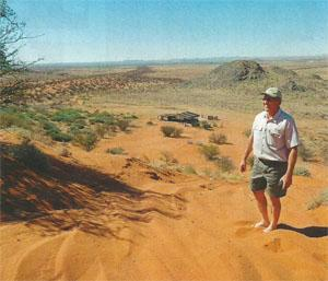 Dirk Malan on a hillside of red Kalahari sand at Blocuso Trust.