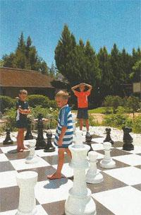 Children play a more physical game of chess on the giant-sized chessboard at The Falls Guest House