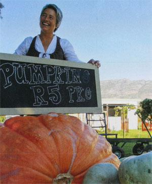 Ruth Goodman's giant pumpkin dwarfs the other produce at her weekly vegetable market.