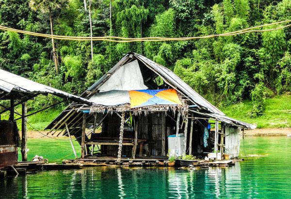 Surrounded by the oldest evergreen rainforest, the isolated lake house floats on the Cheow Man lake in the Khao Sok National Park. Faint sounds of monkeys are heard echoing in the distance.