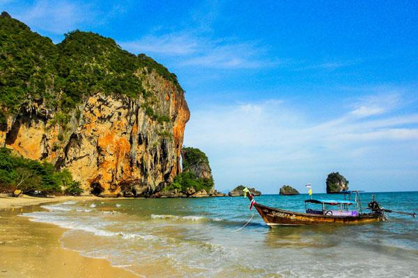 Seen here is Phra Nang Beach caressed by majestic lime stone mountains – a destination for splendid photographs. A rugged long-tail boat floats in the crystal clear warm water, one form of transportation common amongst locals and tourists.
