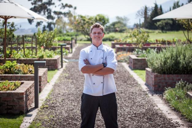 Caption:  Longridge restaurant chef, Bruce von Pressentin, in the extensive organic herb & vegetable garden on the Estate.