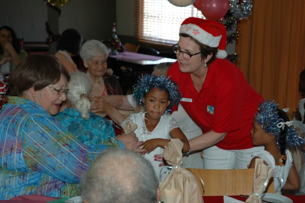 Lion's Club member Paula Lang with the children distributing presents
