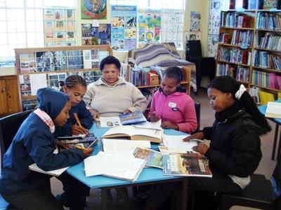 Van die leerlinge sit by Lillian terwyl sy hulle help en ondersteun met hul huiswerk.