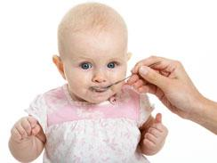 Baby girl being fed with solid food with a spoon