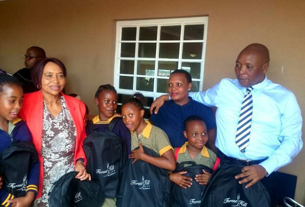 Member of the Tshwane mayoral committee Nozipho Tyobeka-Makeke (left) and Johannesburg North district director for education Sipho Mkhulisi (far right) hand over school backpacks, sponsored by Forest Hill City shopping centre, to delighted pupils from Orefile Primary School in Olievenhoutbosch. With them is Gloria Papo (second from right) of Lemoleabo Caterers.
